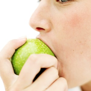 Teen Girl (15-17) Biting into a Green Apple --- Image by © Royalty-Free/Corbis